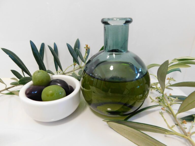 Black and green olives, olive oil in a glass bottle and olive leaves from a local olive tree.