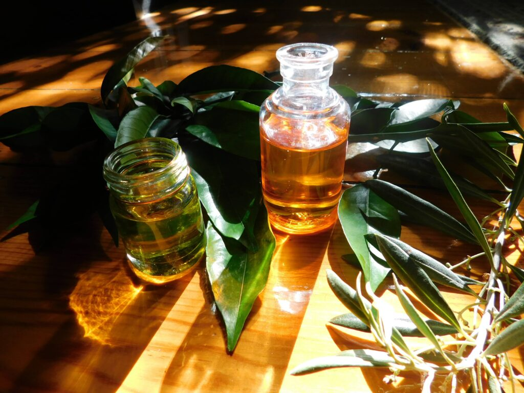 Rosehip and Jojoba oils, looking golden through the sunlight and surrounded by orange and olive leaves.