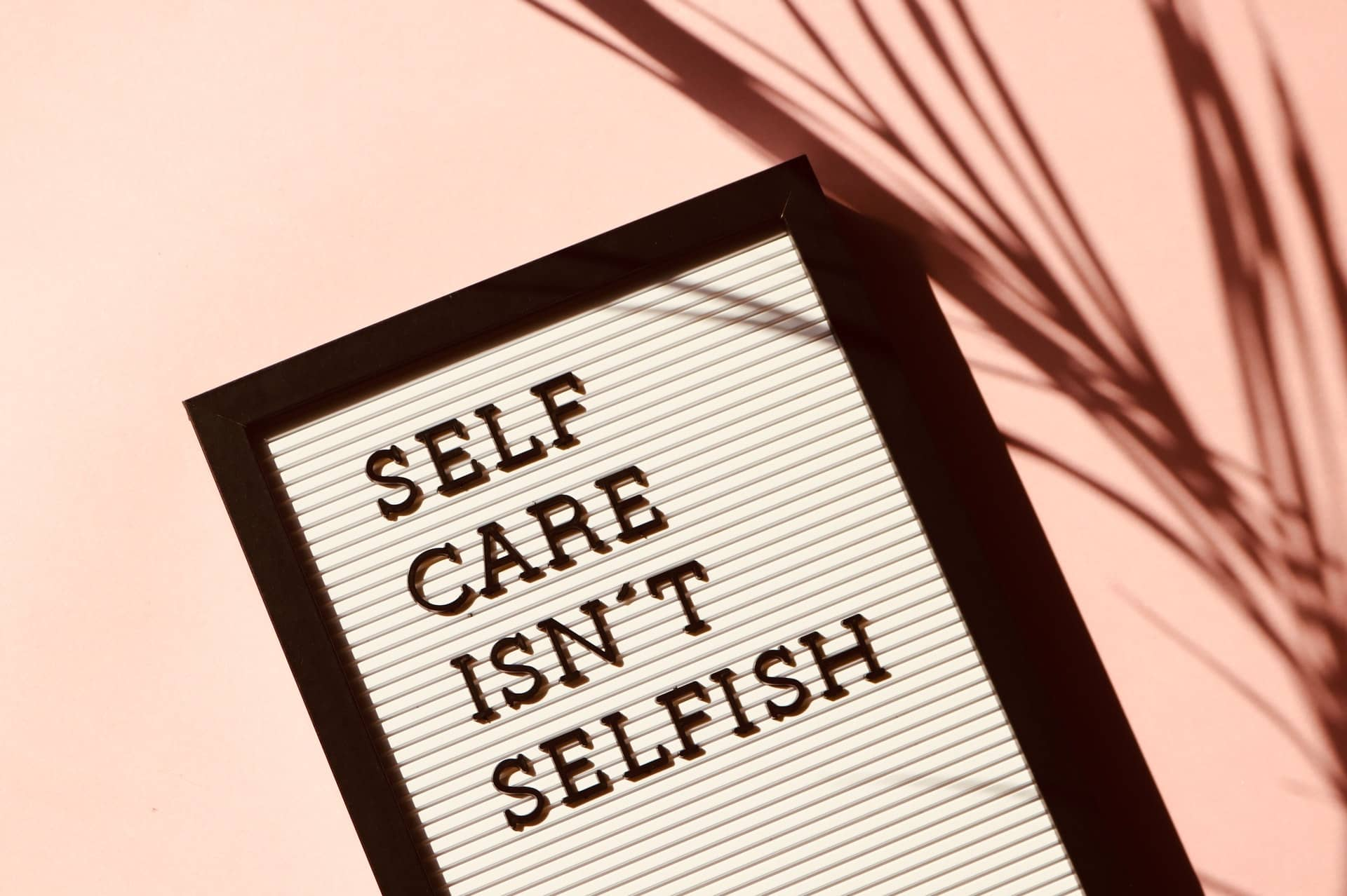 """A sign saying """"Self care isn't selfish"""". It is important to note that caring for yourself is a necessity."""